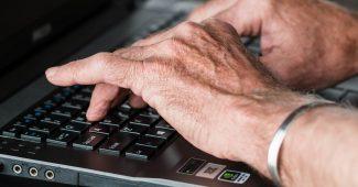 Gigtplagede hænder der skriver på laptop