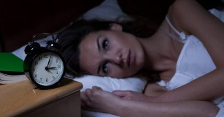 Kvinde der ikke kan sove med et vækkeur ved sin side