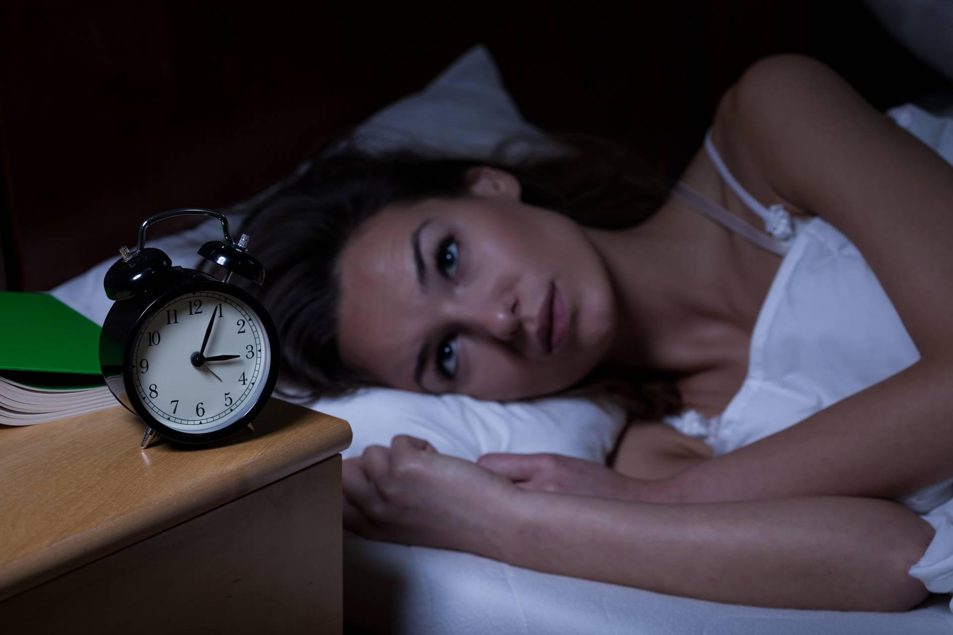 En kvinde der ligger i sin send og kigger på vækkeuret