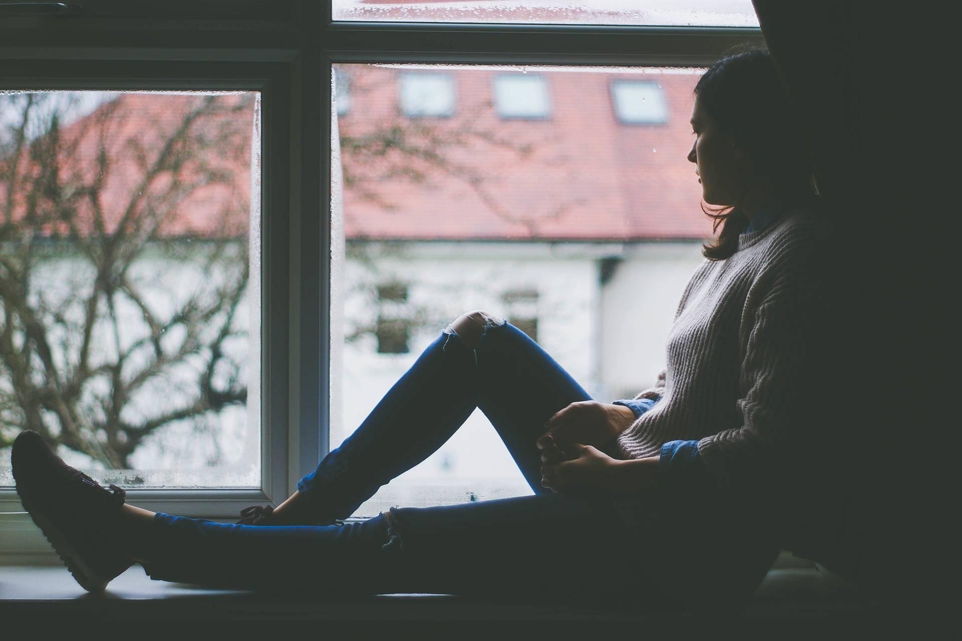 Trist kvinde der sidder i et vindue
