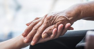 En ung hånd holder en ældre rynket hånd