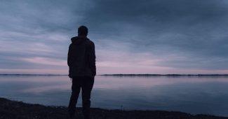 Mand alene ved en sø