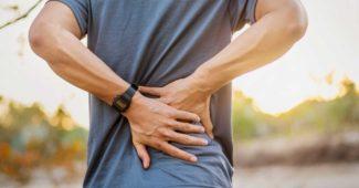 Mand der tager sig til ryggen, fordi han har muskelsmerter