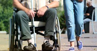 En kørestolsbruger med multipel sklerose og en kvinde der går