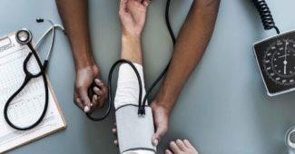 En kvinde får målt blodtryk på sin arm