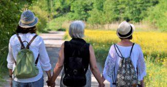 Tre kvinder går en tur og holder hinanden i hænderne